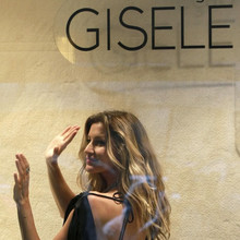 Brazilian model Gisele Bundchen waves during a photocall to present her collection created by C&A store in Sao Paulo